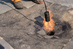Roofer doing repair roof drain. Royalty Free Stock Photography
