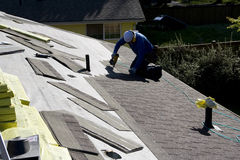 Roofer fixing roofing new roof. A roofer was installing new shingles on a house Stock Photography