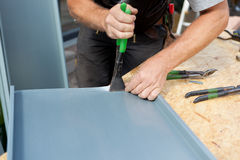 Roofer folding a metal sheet using special pliers Royalty Free Stock Photography