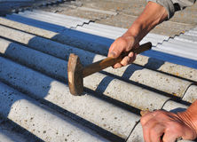 Roofer hammering nail in asbestos old roof tiles. Roofing constr. Uction Royalty Free Stock Photo