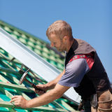 Roofer hammering nails into beams Stock Photos