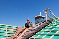 Roofer hammering nails on the beams Royalty Free Stock Photo