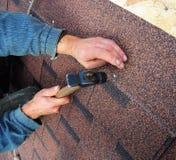 Roofer installeert de dakspanen van het bitumendak - close-up op handen Roofin Stock Afbeelding