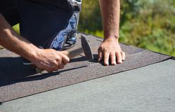Roofer installing asphalt shingles on house construction roof corner with hammer and nails. Roofing construction. Roofing contractor install roof tiles royalty free stock photography