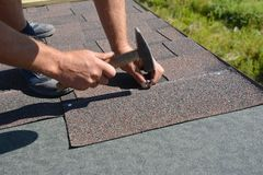 Roofer installing Asphalt Shingles on house construction roof corner with hammer and nails. Roofing construction with Asphalt. Shingles stock photography