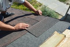 Roofer installing asphalt shingles on house construction roof corner. Roofing construction. Roofing contractor install roof tiles royalty free stock photos
