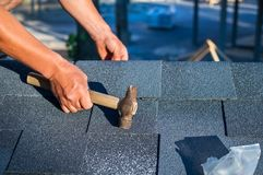 Roofer installing corner bitumen roof shingles with hammer and nails royalty free stock image