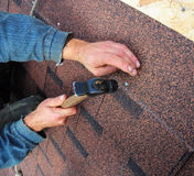 Roofer installs bitumen roof shingles - closeup on hands. Roofin. Roofer installs Asphalt Shingles or  bitumen roof shingles - closeup on hands. Roofing repair Stock Image