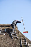 Roofer with ladders on a thatched roof to remove moss and dirt w Royalty Free Stock Image