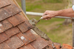 Roofer Laying Cement For Edge Tile On Roof Eaves Stock Photography