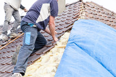 A roofer laying tile on the roof Royalty Free Stock Image
