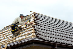 Roofer laying tiles. Middle aged roofer laying tiles on unfinished house building royalty free stock photo