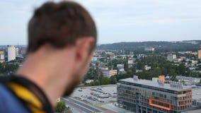 Roofer masculino extremo que mira abajo del top del rascacielos, adicto a la adrenalina almacen de video