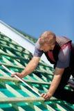 Roofer mesurant les faisceaux de toit Photographie stock