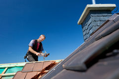 Roofer molding tiles with a hammer Stock Images