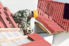 Roofer nailing clay tile Royalty Free Stock Photo