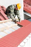 Roofer nailing clay tile. Builder worker at roofing works on clay tiling with hammer screw nails Stock Photo