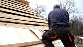 Roofer nailing the wooden roof tiles on the cedar wooden shingle shake roof stock footage