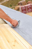Roofer nails lining using construction stapler. Roof under construction. Stock Photos