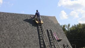 Roofer Installing Roof. A roofer in the process of installing a roof on a new construction house stock photo