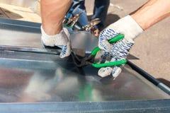 Roofer que dobra uma folha de metal usando alicates especiais com um grande aperto liso Fotografia de Stock
