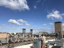 Roofer que examina el tejado plano modificado liso, unidades de la HVAC imagenes de archivo