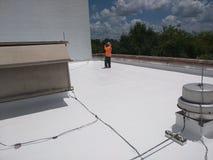 Roofer que examina un tejado plano comercial, techumbre de EPDM imagen de archivo