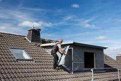 Roofer que lleva un pedazo del metal a la ventana abuhardillada imagenes de archivo