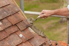 Roofer que pone el cemento para el azulejo del borde en aleros de la azotea Fotografía de archivo