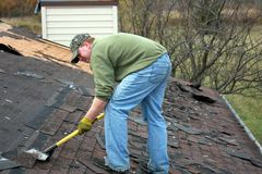 Roofer removing shingles. Construction roofer removing shingles on a house roof Royalty Free Stock Images