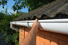 Roofer repair and renovate roof gutter on old brick house asbestos roof stock photos