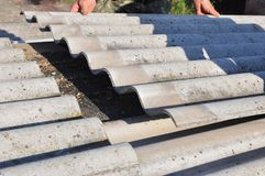 Asbestos removal. Roofer replace damaged asbestos tile. Roofing construction. royalty free stock photo