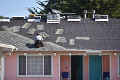 Roofer replacing the roof tiles at a pink colored motel. Male roofer stapling asphalt roof tiles to repair a roof on a motel. Motel is pink in color with blue Royalty Free Stock Images