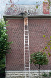 Roofer Replacing Slate on Roof. Roofing contractor on ladder replacing slate on roof Royalty Free Stock Images