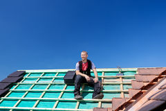 Roofer resting on top of a roof Royalty Free Stock Photography