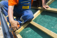 A roofer on the rooftop prepairing wooden construction. Stock Photography