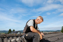 Roofer sitting on the rooftop Royalty Free Stock Photos