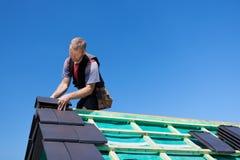 Roofer som monterar kantade tegelplattor till taket royaltyfria bilder