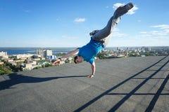 Roofer steht auf seinen Händen am Rand des Dachs stockfoto