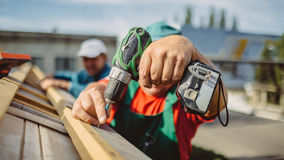 Roofer using a drill is fastening a cap to a house roof stock photos