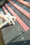 A roofer using hammer to nail tiles to wooden roof battens Royalty Free Stock Image
