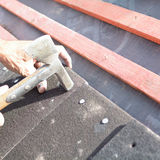 A roofer using hammer to nail tiles to wooden roof battens Stock Images