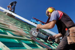 Roofer using a hand circular saw Royalty Free Stock Photos