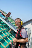 Roofer using safety goggles and ear mufflers Stock Photography