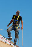 Roofer at Work. Roofer with safety harness shingling a roof with a steep pitch