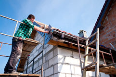 Roofer at work. Standing on scaffolding, installing roof tiles royalty free stock photos