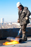 Roofer worker installing a roll of roofing felt. Roofer man worker in a helmet installing a roll of roofing felt by means of gas blowpipe torch Royalty Free Stock Photography