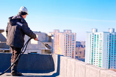 Roofer worker installing roofing felt. By means of gas blowpipe torch Stock Photography