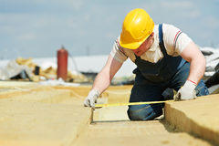 Roofer worker measuring insulation material. Builder worker inspecting insulation material by measuring tape at roof Royalty Free Stock Photography