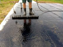 Roofer worker painting bitumen praimer at concrete surface by the roller brush Waterproofing royalty free stock photo